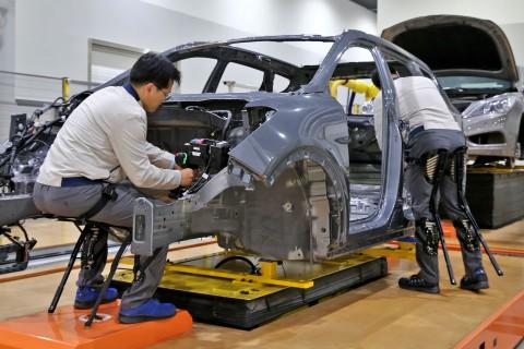 현대자동차 직원이 의자형 착용로봇을 착용하고 작업하고 있다