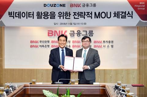 더존비즈온 김용우 회장(오른쪽)과 BNK금융그룹 김지완 회장이 양해각서를 교환하고 있다