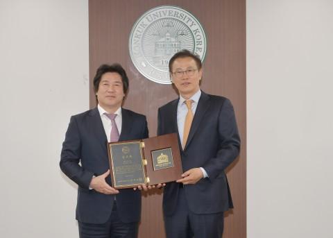 (왼쪽부터)민상기 건국대 총장이 건국대에 발전기금 20억원을 기부한 엠디엠그룹 문주현 회장에게 감사패를 수여하고 있다
