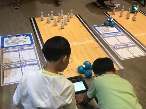 2019 과학학습 교구 박람회에서 대시를 활용한 볼링 게임 워크숍에 참가한 아이들이 대시 전용앱인 블록클리를 활용한 코딩으로 대시를 움직여 볼링 공을 쓰러뜨리는 활동 체험을 하고 있다
