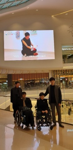 한국장애예술인협회가 개최하는 장애인예술로 아름다워지는 대한민국 참여 작가들이 대형 전광판 앞에서 기념촬영을 하고 있다