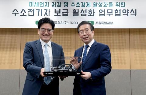 왼쪽부터 현대차 공영운 사장과 서울시 박원순 시장이 수소전기차 넥쏘 절개차 모형을 들고 기념촬영을 하고 있다