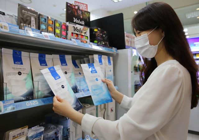 GS25에서 고객이 일회용 마스크를 살펴보고 있다