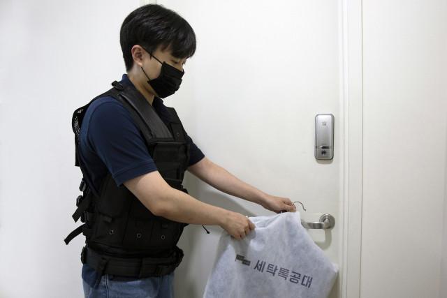 세탁특공대 직원이 고객 집앞으로 세탁물을 새벽 배송하고 있다