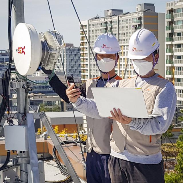 SKT 엔지니어들이 5G 무선 프론트홀 장비를 구축하고 있다