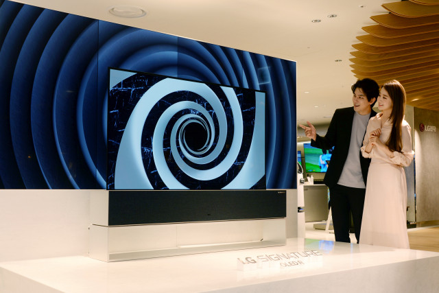 서울 중구 소공동 소재 롯데백화점 본점에서 고객들이 화면을 말았다 펼치는 'LG 시그니처 올레드 R'을 살펴보고 있다
