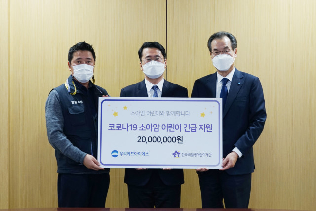 우리FIS 이동연 대표이사(오른쪽)와 김진근 노동조합 위원장(왼쪽)이 한국백혈병어린이재단 서선원 사무총장(가운데)에게 기금을 전달하고 있다