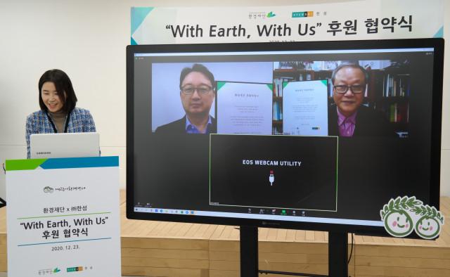 화면 속 왼쪽부터 한섬 조준행 부사장과 환경재단 최열 이사장이 후원 협약서를 들고 기념 촬영을 하고 있다