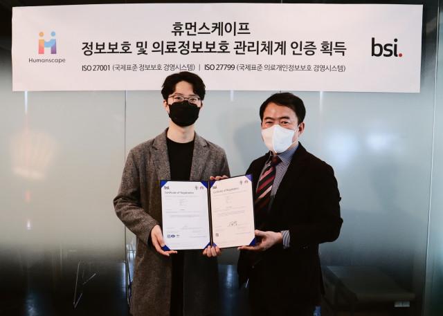 ISO 취득식에서 왼쪽부터 이태우 휴먼스케이프 최고기술경영자와 송경수 BSI Korea 총괄 책임이 기념 촬영을 하고 있다