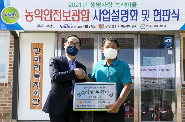 왼쪽부터 생명보험사회공헌재단 송기정 상임이사와 관마마을 김영화 이장이 농약안전보관함 현판식에서 기념 촬영을 하고 있다