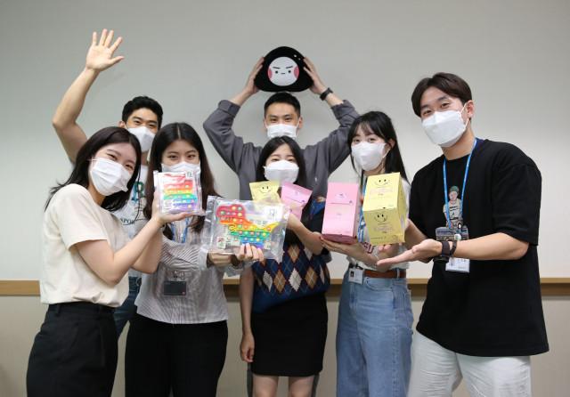 GS리테일에서 MZ세대만 모여 신상품 개발을 위해 구성한 갓생기획 프로젝트 멤버들이 신상품을 들고 기념 촬영을 하고 있다
