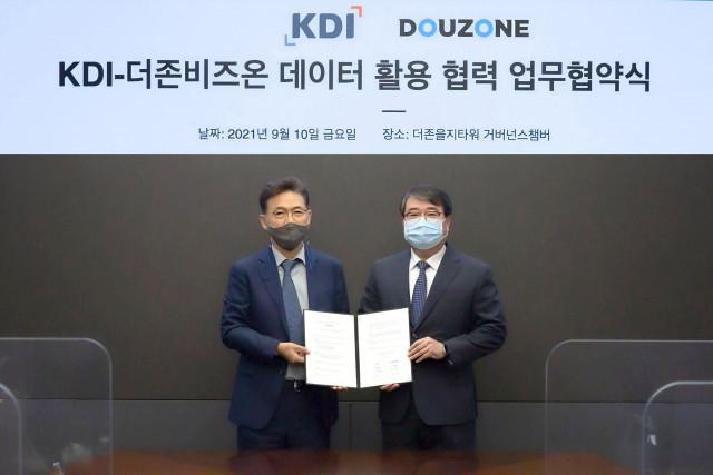 왼쪽부터 홍장표 한국개발연구원장과 김용우 더존비즈온 김용우 대표가 업무 협약을 맺고 기념촬영을 하고 있다