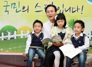 KB창작동화제 시상식에서 민병덕 은행장(사진 왼쪽 두번째)이 시상식에 참석한 어린이들에게 창작동화집<동화는내친구>를 읽어주고 있다. (사진제공: KB국민은행)
