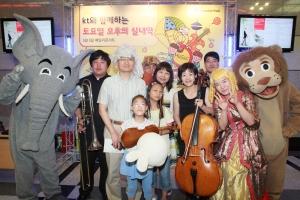 KT는 어린이 날을 맞이하여 5일 서울 양천구 목동에 위치한 KT체임버홀에서 '패밀리 클래식 콘서트'를 열었다. 콘서트를 관람한 어린이들(과 가족들)이 '동물의 사육제'에 등장하는 동물인 사자, 코끼리 및 공연 연주자들과 함께 포즈를 취하고 있다. (사진제공: KT)