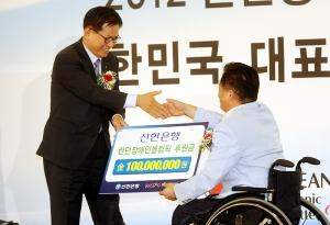 2012 런던장애인올림픽 선수단 결단식에서 신한은행 서진원 은행장(좌측)이 장춘배 선수단 단장(우측)에게 격려금을 전달 하고 있는 모습. (사진제공: 신한은행)
