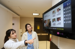LG유플러스는 월 3만원대의 경제적인 요금으로 중소기업 및 소상공인의 사업에 도움이 되는 기업용 IPTV 서비스 U+Biz tvG 스마트 솔루션을 세계 최초로 선보인다고 22일 밝혔다. 사진은 강남 소재 더조은병원에서 간호사들이 U+Biz tvG 스마트 솔루션 서비스를 적용한 TV화면 속 진료 대기표를 보는 모습.
