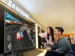 삼성전자 모델이 삼성 딜라이트에서 삼성 스마트 TV로 다양한 신규 게임을 즐기고 있다 (사진제공: 삼성전자)