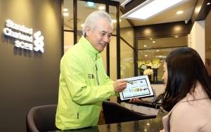 박종복 한국SC은행장이 9일 부산 신세계백화점 센텀시티점에 문을 연 뱅크샵에서 1호 손님에게 태블릿PC 기반의 모빌리티플랫폼을 활용해 금융상담을 하고 있다 (사진제공: 한국스탠다드차타드은행)