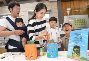 아이와 부모가 함께 분유캔을 이용해 그린팟을 만드는 모습