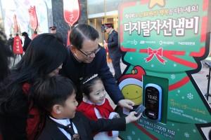 어린이가 디지털자선냄비에 교통카드를 태그하여 기부하고 있다