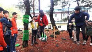 국립평창창소년수련원 야외 활동 전문 지도자가 문경새재유스호스텔에서 연수 참가자들에게 숲 밧줄 놀이 방법을 교육하고 있다