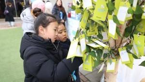 행사에 참여한 시민들이 희망 트리에 메시지를 적고 있다