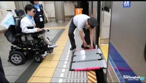 일본 역무원의 안내를 받아 전동휠체어로 전철을 이용하고 있다