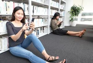 블라이스 이용자가 도서관에서 스마트폰을 이용해 웹소설을 읽고 있다