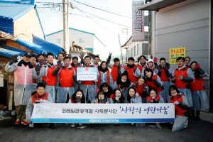 봉사단 카드를 들고 있는 김순철 대표이사(왼쪽윗줄 8번째)와 직원들이 사랑의 연탄나눔 봉사활동을 마치고 모였다
