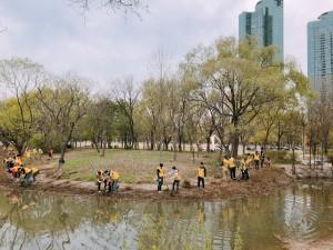 기업 자원봉사 활동으로 서울숲 수변에 가우라를 심고 있다