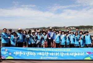 수협중앙회 임준택 회장을 비롯한 임원들과 여성어업인들이 태풍으로 밀려온 해양쓰레기 정화 활동을 하고 기념 촬영을 하고 있다