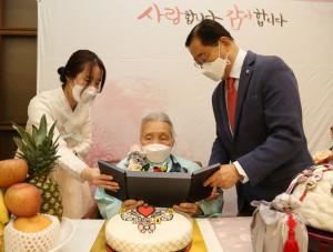 사회복지법인 가정복지회 변상길 대표이사가 초청된 김연심 어르신에게 기념패를 전달하고 있다