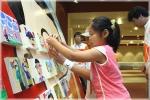SK㈜의 '행복캠프'에서 아이들이 직접 그린 그림을 붙히고 있는 장면과 서울시청 앞 광장에 전시된 초대형 그림판. 총 900장의 그림이 '함께하는 행복한 세상'이라는 주제로 전시됨
