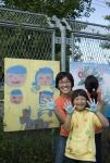 샘표 간장공장에서 열린 '수확하는 예술가'행사에 참여한 가족, 손으로 그린 벽화를 배경으로 가족이 환하게 웃고 있다.
