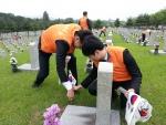 29일 국립서울현충원 결연묘역에서 한화 임직원들이 정성스럽게 묘역을 단장하고 있다.