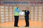 차흥봉 한국사회복지협의회장(왼쪽)이 서경석 우리마포복지관장(오른쪽)에게 독거어르신용 생필품꾸러미를 전달하고 기념촬영을 했다.