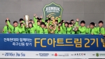 FC아트드림 2기 참여 아동들이 전북현대모터스FC의 과거 우승컵을 들고 기념 촬영하고 있다