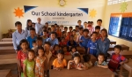 이글루시큐리티 임직원들이 캄보디아 아워스쿨 놀이방에서 아이들과 기념촬영을 하고 있다