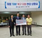 롯데건설 전략기획부문장 이부용 상무(왼쪽에서 세번째)가 울산시 중구 태화동 주민센터에서 기부금을 전달하고 있다