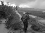진흙탕이 된 길을 따라 아이를 안고 방글라데시로 탈출하고 있는 한 로힝야 여성