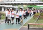300여명의 회원과 시각장애인들이 도림천변 산책로를 걷고 있다