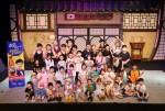 공연이 끝난 뒤 배우들과 어린이들이 무대 위에서 함께 기념촬영을 하고 있다