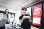 SK텔레콤 모델들이 서울 명동에 위치한 대리점에서 '갤럭시 노트10'으로 5G 서비스를 사용하고 있다