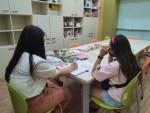이룸마을학교 담당자와 아동이 개별입학식을 진행 중이다