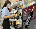 GS25에서 모델이 와인을 살펴보고 있다