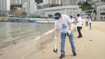국제 해안 클린업 데이 행사에 참가한 동원산업 직원이 부산 송도해수욕장에서 쓰레기를 수거하고 있다