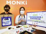 공유주방 '먼슬리키친 강남점'에서 배달 라이더가 포장음식이 든 종이백을 들고 있고, 레스토랑 직원이 '2021 딜리버리위크 여름편'을 소개하고 있다