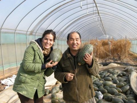한국 농가를 찾은 외국인 우퍼가 한국인 농부와 함께 추수한 호박을 들어보이며 웃고 있다.