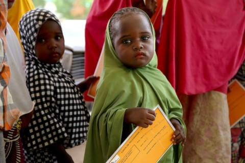 나이지리아 난민들을 위해 백신 캠페인을 실시하고 있다. 어린 소녀가 백신 카드를 손에 쥔 채 차례를 기다리고 있다