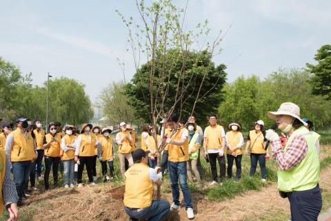 까사미아 임직원들이 인솔강사의 안내에 맞춰 나무를 심고 있다